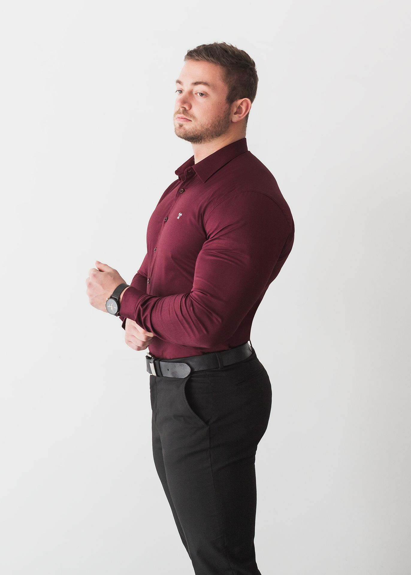 The first of our types of product photography to feature a model. This image shows a muscular male model in a tight-fitting red shirt. The shirt is designed for muscular men, and fits well. He stands at an angle against a white background.