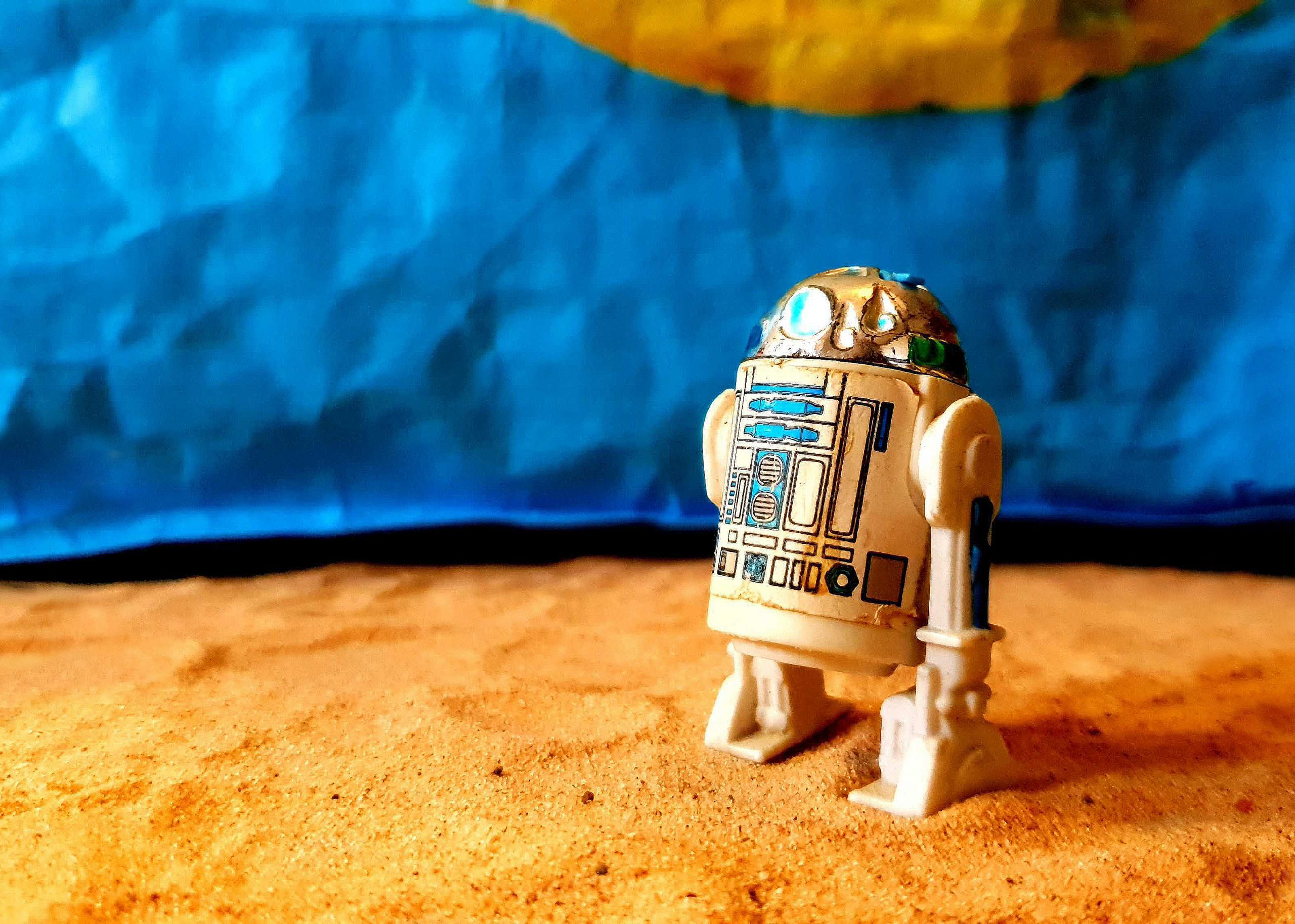 Emma's submission to the Great British Photography Challenge shows R2D2 from Star Wars stood on an area of sand. Behind is a blue sky, which is actually a Lidl shopping bag.