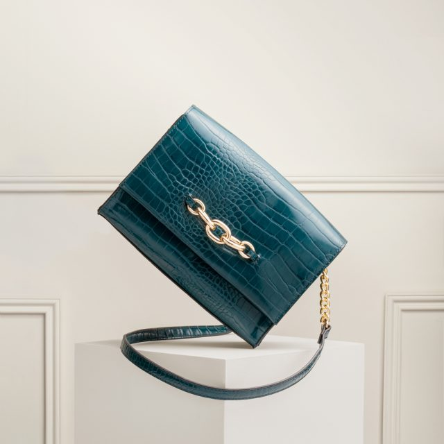 A shot from a creative still life shoot; Amelia was shoot assistant. This shot shows a cross-body handbag balanced on its corner, with a panelled wall in the background.