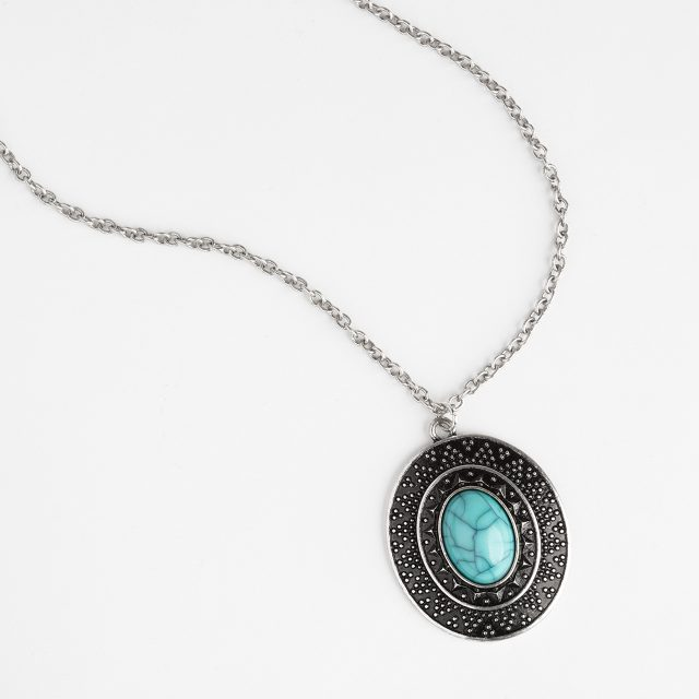 An eCommerce product shot showing a necklace laid out elegantly on a light grey background.