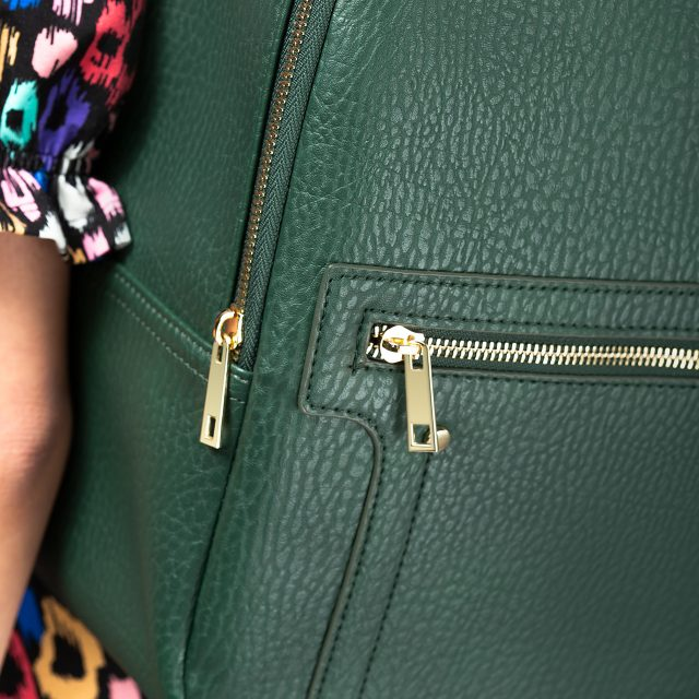 A close up eCommerce model shot showing the zips on a faux-leather backpack