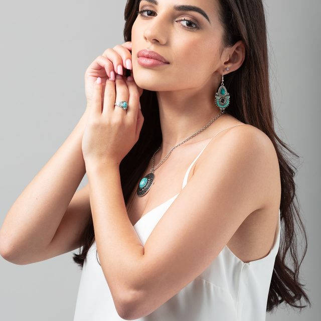 Model photography showing a model wearing a silver jewellery set. The set includes a ring, pair of earrings, and a necklace.
