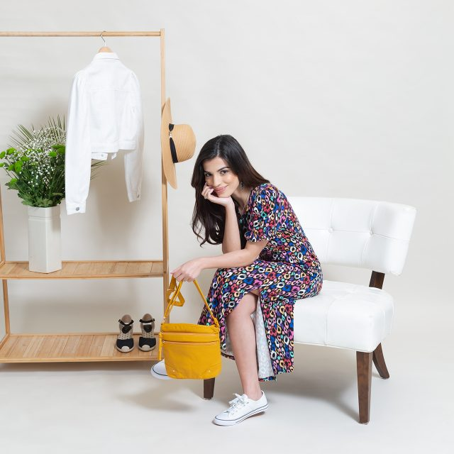 A model eCommerce shot showing a model sat down in front of a clothes rail. She's holding a yellow bag and wearing a bright, colourful dress.