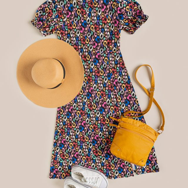 An eCommerce flatlay shot, taken from above. It shows the same colourful dress from earlier arranged with a yellow bag, white trainers, and a beige sun hat.