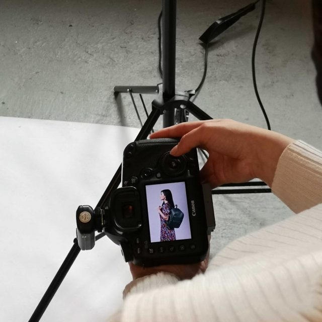 This photograph looks over the shoulder of a photographer reviewing an eCommerce shot they've just taken.